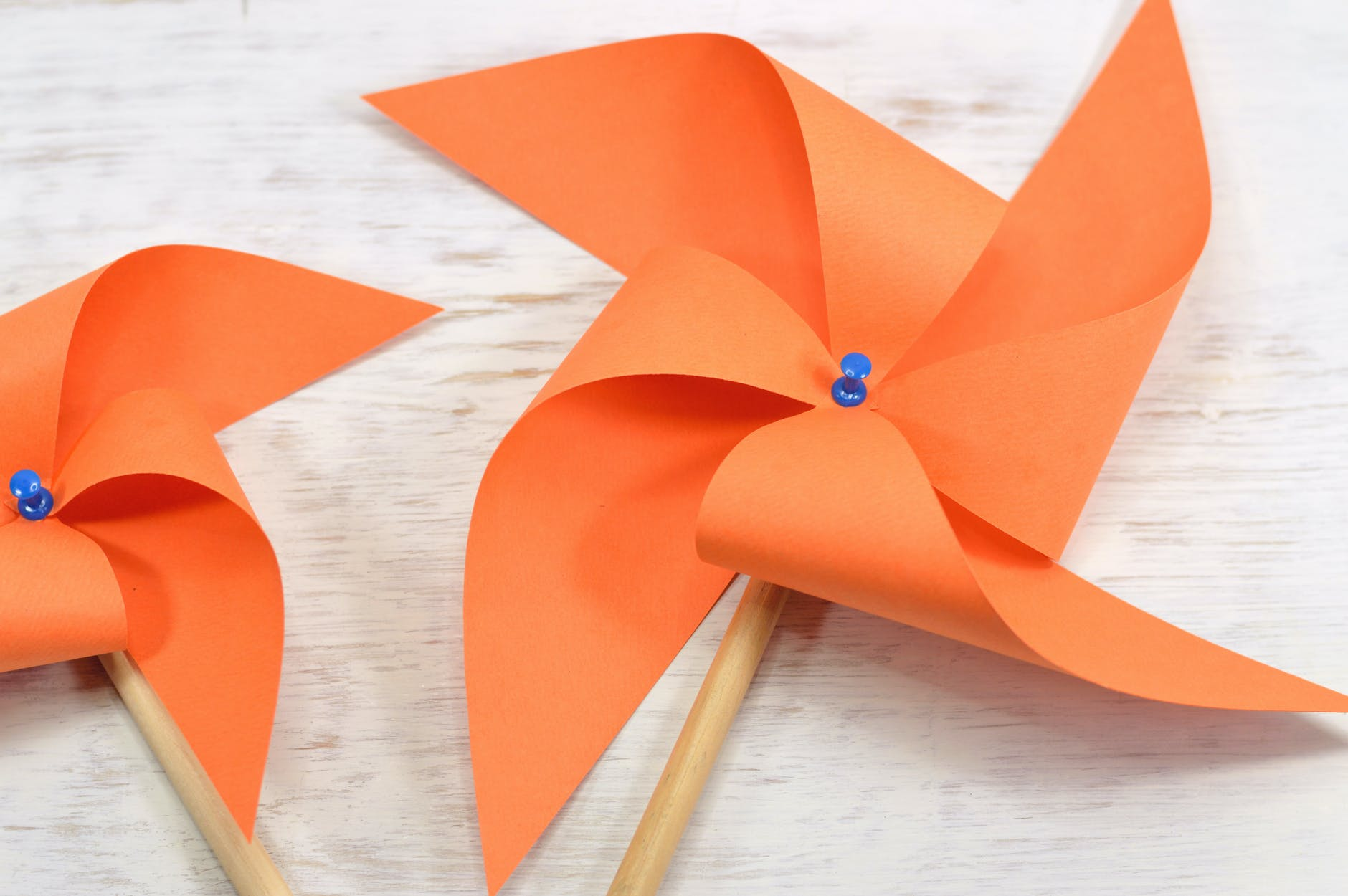 two orange paper windmills